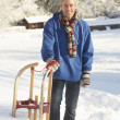 Stock Photo: Middle Aged Man Standing In Snowy Landscape Holding Sledge