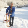 Royalty-Free Stock Photo: Middle Aged Man Standing In Snowy Landscape Holding Sledge