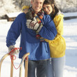 Young Couple Standing In Snowy Landscape Holding Sledge — Foto de Stock