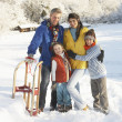 Young Family Standing In Snowy Landscape Holding Sledge — Stock Photo #4837586