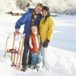 Young Family Standing In Snowy Landscape Holding Sledge — Stock Photo #4837587