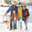 Young Family Standing In Snowy Landscape Holding Sledge — Stock Photo #4837589