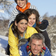 Young Family Having Fun In Snowy Landscape - Stock Photo