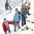 Family Enjoying Walk Through Snowy Landscape - Stock Photo