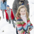 Family Enjoying Walk Through Snowy Landscape — Stockfoto