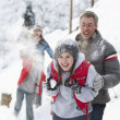 Young Family Having Snowball Fight In Snowy Landscape - Stock Photo