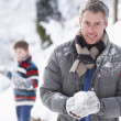 Father And Son Having Snowball Fight In Winter Landscape - Stockfoto