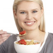 Young Woman Eating Bowl Of Healthy Breakfast Cereal In Studio — Stock Photo