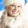 Young Woman Wearing Warm Winter Clothes And Fur Hat In Studio - Foto Stock
