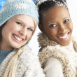 Two Young Women Wearing Warm Winter Clothes Holding Snowball In - Stock Photo