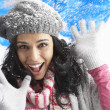 Young Woman Wearing Warm Winter Clothes And Hat Being Hit By Sno - Stockfoto