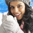Young Woman Wearing Warm Winter Clothes And Hat Holding Snowball - Stockfoto