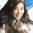 Young Woman Wearing Warm Winter Clothes Holding Snowball In Stud - Foto Stock