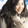 Young Woman Wearing Warm Winter Clothes Holding Snowball In Stud - Zdjęcie stockowe