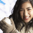 Young Woman Wearing Warm Winter Clothes Holding Snowball In Stud - Stok fotoğraf