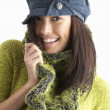 Fashionable Young WomanWearing Cap And Knitwear In Studio - Стоковая фотография