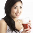 Young Woman Enjoying Healthy Drink In Studio - Stock Photo