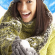 Young Woman Wearing Warm Winter Clothes And Hat Holding Snowball - Foto Stock