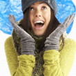 Young Woman Wearing Warm Winter Clothes And Hat Throwing Snowbal - Foto Stock