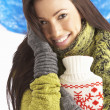 Young Woman Wearing Warm Winter Clothes Holding Hot Water Bottle - 图库照片