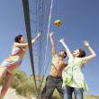 Royalty-Free Stock Photo: Group Of Teenage Friends Playing Volleyball On Beach
