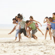 Stock Photo: Group Of Friends Running Along Beach Together