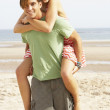 Young Couple Having Piggyback Fun On Beach — Stock Photo