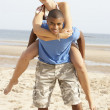 Royalty-Free Stock Photo: Young Couple Having Piggyback Fun On Beach