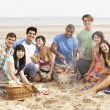group of friends enjoying barbeque on beach together — Stock Photo