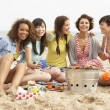 group of girls enjoying barbeque on beach together — Stock Photo