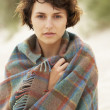 Young Woman Standing In Sand Dunes Wrapped In Blanket - Lizenzfreies Foto