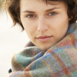 Young Woman Standing In Sand Dunes Wrapped In Blanket - Foto Stock