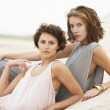 Two Fashionably Dressed Attractive Young Women Laying Amongst Sa — Stock Photo