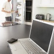 Young Man Fixing Snack In Kitchen With Laptop In Modern Kitchen — Stock Photo