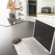 Young Woman Fixing Snack In Kitchen With Laptop In Modern Kitche - Stock Photo