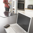 Stock Photo: Young MFixing Snack In Kitchen With Laptop In Modern Kitchen