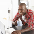 Young Man Using Laptop In Modern Kitchen — Stock Photo