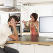 Young Couple Discussing Personal Finances In Modern Kitchen - Stock Photo
