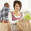 Royalty-Free Stock Photo: Young Couple Unpacking Shopping In Modern Kitchen