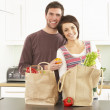 Young Couple Unpacking Shopping In Modern Kitchen - Stockfoto