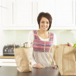 Young Woman Unpacking Shopping In Modern Kitchen — Stock Photo