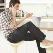 Young Man Relaxing Sitting In Kitchen Talking On Phone — Stock Photo #4838163