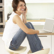 Young Woman Relaxing Sitting In Kitchen Talking On Phone - Photo