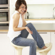 Young Woman Relaxing Sitting In Kitchen Talking On Phone — Stock Photo