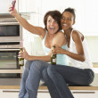 Two Girlfriends Taking Photo With Digital Camera In Modern Kitch — Stock Photo