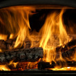 Close Up Of Flaming Logs On Fire - Stock Photo