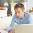 Man Using Laptop To Manage Household Bills Laying On Rug At Home — Stock Photo