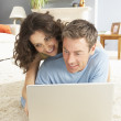 Couple Using Laptop Relaxing Laying On Rug At Home — Stock Photo