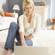 Woman Using Laptop To Manage Household Bills Laying On Rug At Ho — Stock Photo