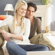 Couple Using Laptop Relaxing Sitting On Rug At Home — Stock Photo